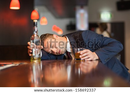 Unmoving businessman holding whiskey glass lying on a counter in a classy bar - stock photo