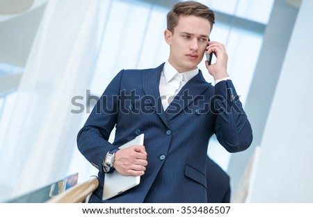 Unpleasant conversation. Confident businessman talking on cell phone and holding a tablet in her hand looking to the side while his colleagues talking in the background. - stock photo