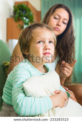 Unpleased young mother scolding little daughter in the living room at home. Focus on girl  - stock photo