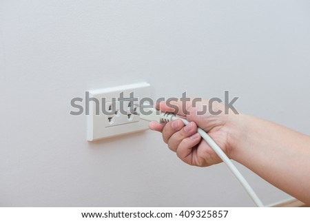 Unplug or plugged in concept,hand holding and pull electric plug - stock photo