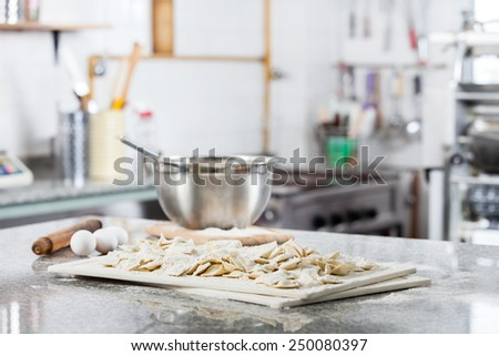 Unprepared ravioli pasta on cutting board with ingredients at countertop in commercial kitchen - stock photo