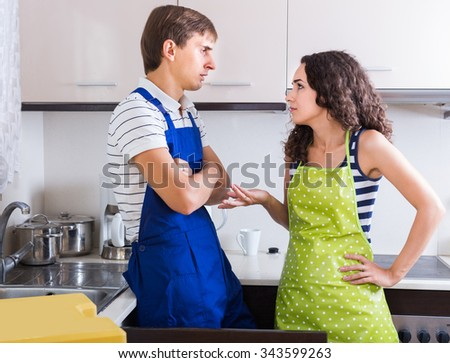 Unprofessional plumber asking furious young woman for bribes indoors - stock photo