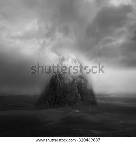 Unreal mountain in the center of a field. The sky is covered in clouds and a beam of light descends - stock photo