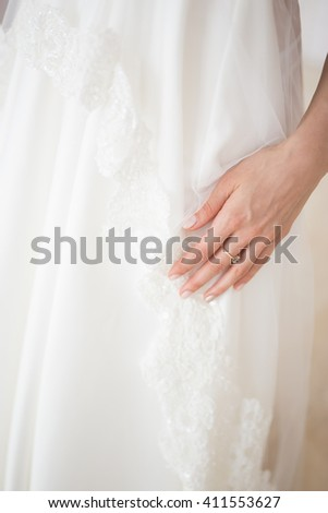 Unrecognizable bride's hand in white wedding dress  - stock photo