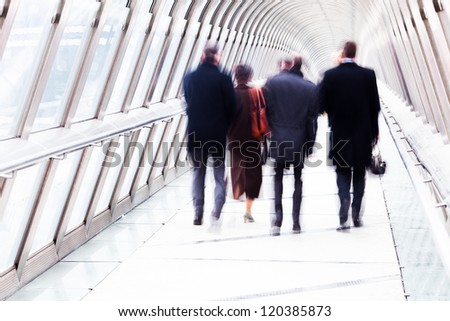 unrecognizable business people walking on a pedestrian bridge with a glass dome - stock photo