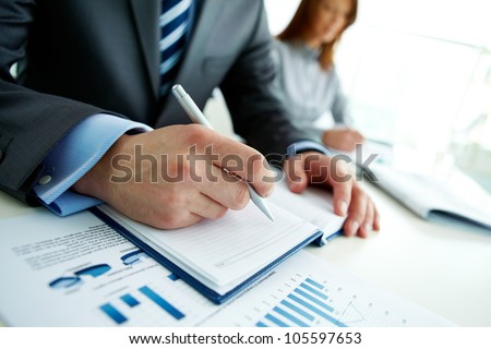 Unrecognizable business person analyzing graphs and taking notes - stock photo