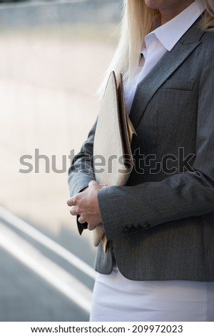 Unrecognizable business woman holding reports. Copy space - stock photo