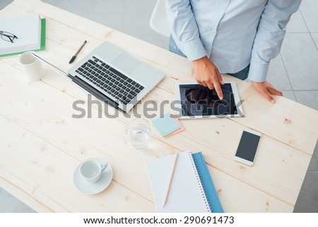 Unrecognizable business woman working at office desk and using a touch screen tablet on a wooden surface - stock photo
