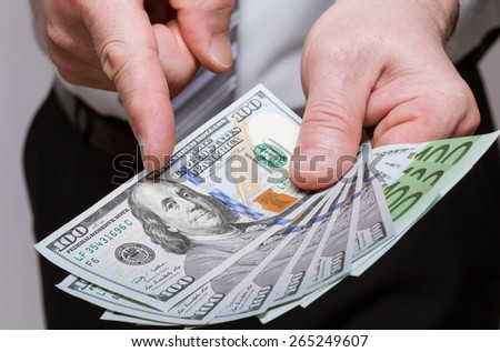 Unrecognizable businessman holding dollars and euro and choosing dollars - stock photo