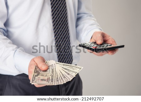 Unrecognizable businessman holding fan of dollar banknotes and calculator - stock photo