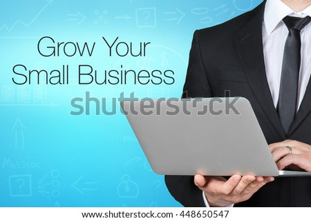 Unrecognizable businessman with laptop standing near text - grow your small business - stock photo