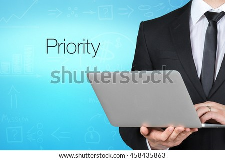 Unrecognizable businessman with laptop standing near text - Priority - stock photo