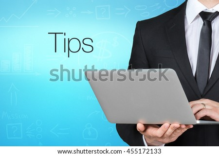 Unrecognizable businessman with laptop standing near text - tips - stock photo