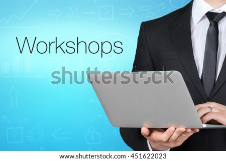 "Unrecognizable businessman with laptop standing near text ""Workshops"" - stock photo"