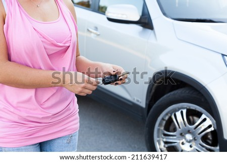 Unrecognizable Caucasian woman with ignition key standing near own vehicle - stock photo