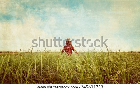 Unrecognizable hipster girl in straw hat walking on summer meadow, rear view. Vintage image - stock photo