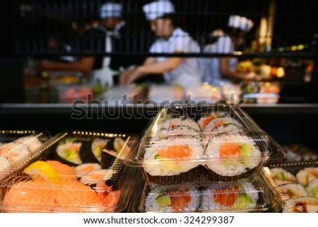 Unrecognizable Japanese workers prepare Sushi rolls . - stock photo