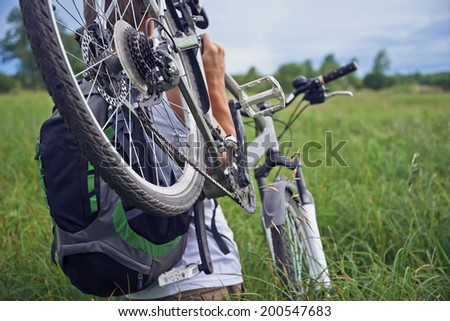 Unrecognizable man carries bike in green meadow in summer, rear view - stock photo