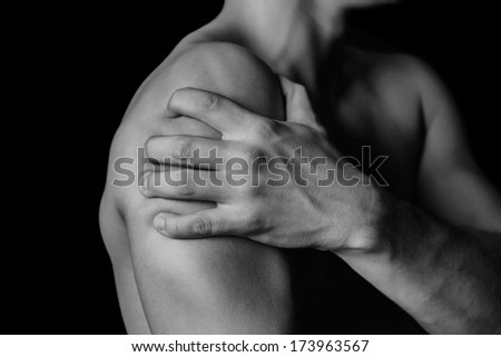 Unrecognizable man compresses his shoulder, pain in the shoulder, side view - stock photo