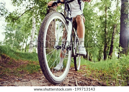 Unrecognizable man is riding bicycle on trail in summer park - stock photo