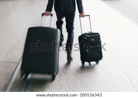 Unrecognizable man with two suitcases hurrying - stock photo
