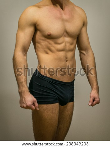 Unrecognizable muscular male body on grey background. - stock photo