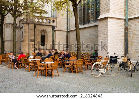 Unrecognizable people sitting on a terrace in Antwerp, Belgium, against the exterior of the cathedral in the city center, a typical relaxation moment in this touristic city - stock photo