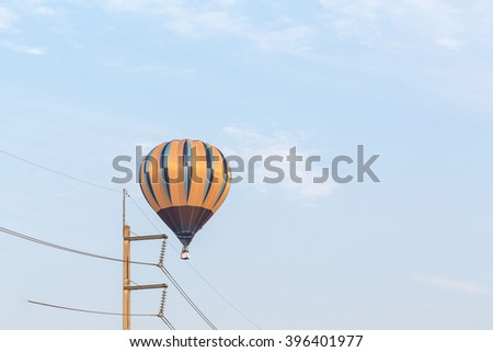 Unrecognizable people traveling in a multicolor balloon  - stock photo
