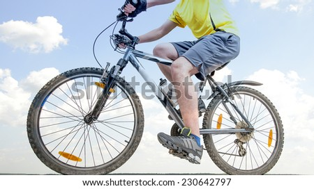 Unrecognizable person No face Mountain Biker on blue sky with clouds background Man wearing yellow sport shirt gray snickers and shorts Empty copy space for inscription - stock photo