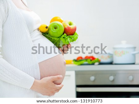 unrecognizable pregnant woman with healthy food in kitchen - stock photo