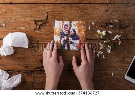 Unrecognizable sad woman holding torn picture of couple in love.  - stock photo
