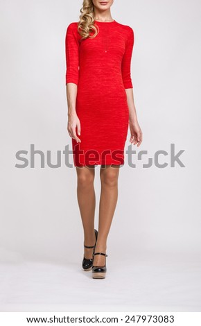 Unrecognizable slender  young woman in a red dress on neutral background - stock photo