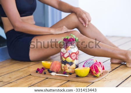 Unrecognizable sportive woman with a healthy breakfast in a mason jar - stock photo