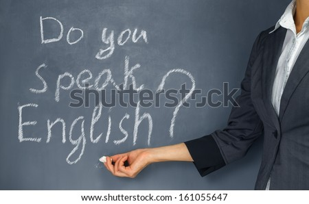 Unrecognizable teacher points to the phrase: Do you speak English? - stock photo