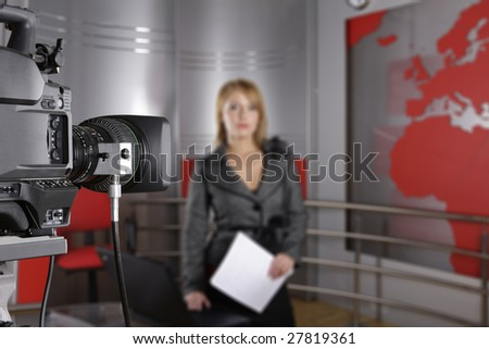 unrecognizable television news reporter in front of the video camera with documents in hand - stock photo
