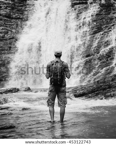 Unrecognizable traveler young man with backpack standing in river and looking at waterfall in summer outdoor, rear view. Monochrome image - stock photo