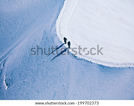 unrecognizable two climbers on the way to a mountain peak in the Alps - stock photo