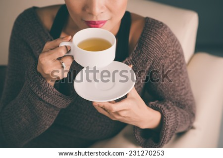 Unrecognizable woman holding a hot cup of tea and blowing on it - stock photo