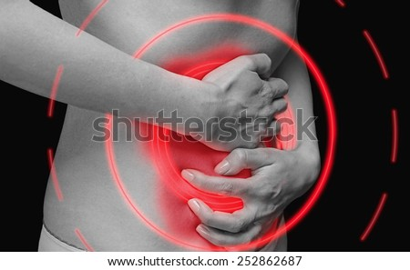 Unrecognizable woman holds her abdomen, side view, abdominal or menstrual pain, monochrome image, painful area of red color. - stock photo