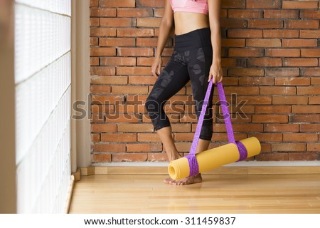 Unrecognizable woman in a yoga studio indoors, against a brick wall with a mat. - stock photo