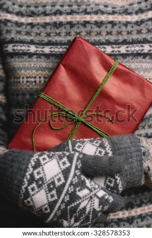 Unrecognizable Woman wearing knit sweater and gloves holding Christmas Gift - stock photo