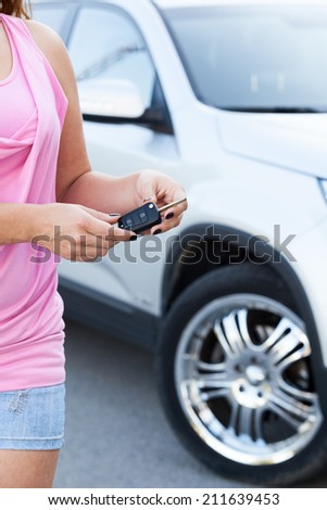 Unrecognizable woman with ignition key standing near new car - stock photo