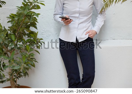unrecognizable young business woman using her smartphone outdoors - stock photo