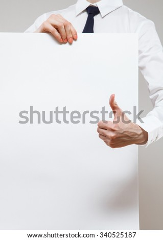 Unrecognizable young businesswoman holding a white poster and showing thumb up on neutral background - stock photo