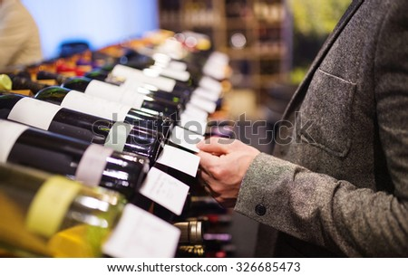 Unrecognizable young man in a wine shop choosing a wine - stock photo