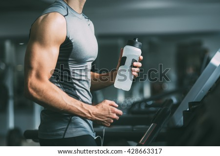 Unrecognizable young man in sportswear running on treadmill at gym and holding bottle of water  - stock photo