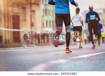 Unrecognizable young runners at the city race - stock photo