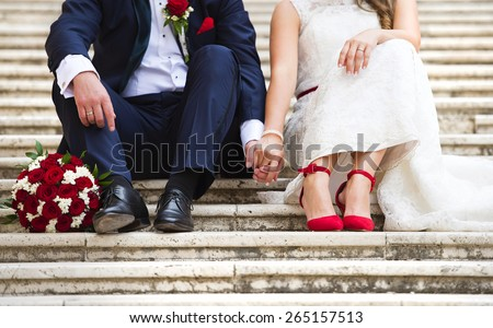 Unrecognizable young wedding couple holding hands as they enjoy romantic moments outside on the stairs - stock photo