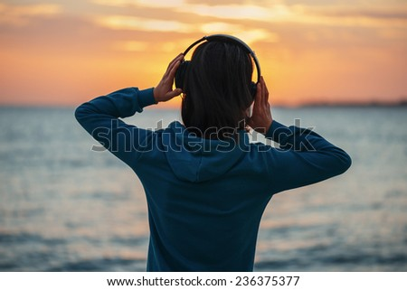 Unrecognizable young woman in headphones enjoying beautiful sunset over the sea, rear view - stock photo