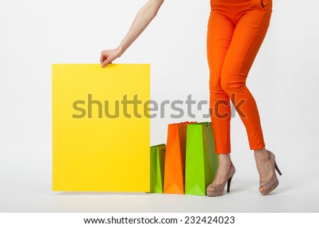 Unrecognizable young woman in orange pants holding blank yellow paper standing near multicolored shopping bags, closeup shot - stock photo